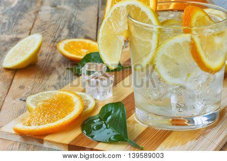 orange lemon leaves glass homemade lemonade ice on old wooden table closeup