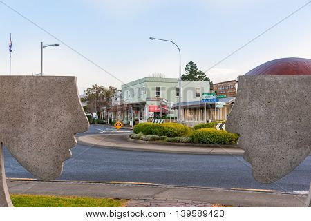 Matakana, New Zealand - July 15, 2016; street scene from intersection of Matakana Valley Road and Leigh Road business buildings with silhouette concrete face profiles public art framing image