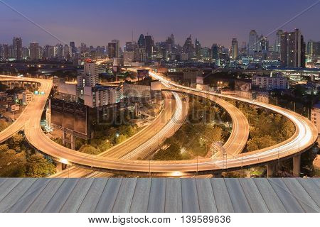 Opening wooden floor, Aerial view highway road curved with city downtown background during twilight