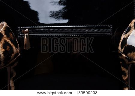 Black handbag and women shoes close-up. tiger.