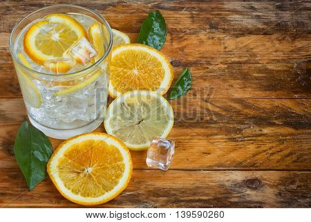 glass homemade lemonade orange lemon and ice stands on an old rustic wooden table