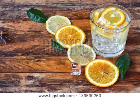 glass homemade lemonade orange lemon stands on old wet rustic wooden table
