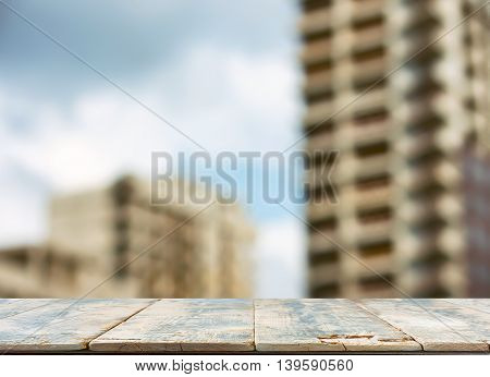 blurred background city new construction wooden plank table in foreground
