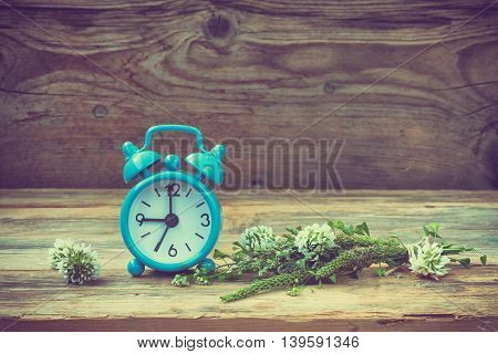 Blue retro alarm clock summer wildflowers on a wooden table toned photo