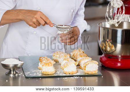 Pastry chef decorating with icing sugar some profiteroles