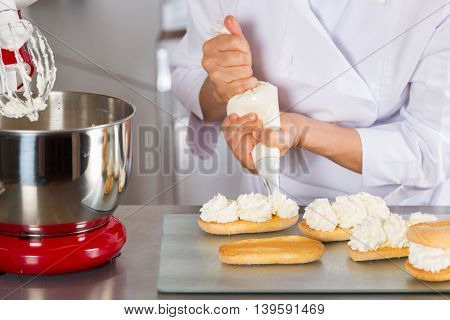 Chef pastry cream filling some a biscuits