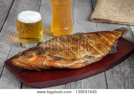 Smoked fish and beer, on the surface of the old gray boards
