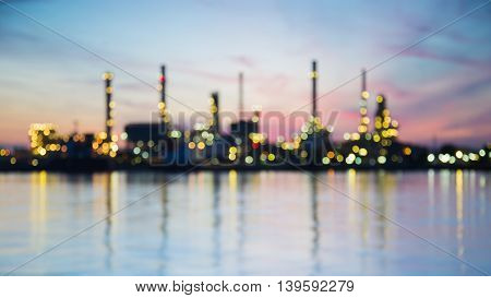 Blurred bokeh lights, heavy oil refinery river front with sunrise sky background