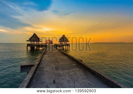 Waking path leading to ocean with beautiful dramatic sunset sky background, natural landscape