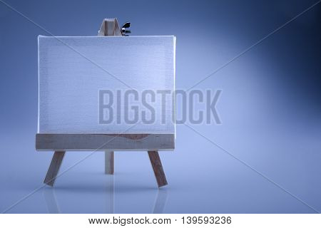 Small easel with a blank canvas with blue effect white balance