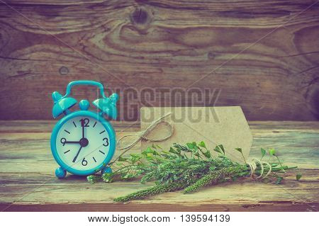 Blue retro alarm clock summer wildflowers paper label on a wooden table toned photo