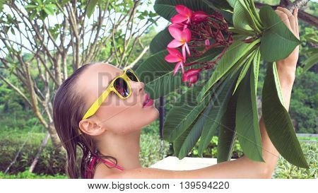 Closeup of sexy young woman wearing bikini and yellow sunglasses with wet hair smelling tree flower at rooftop on a sunny day