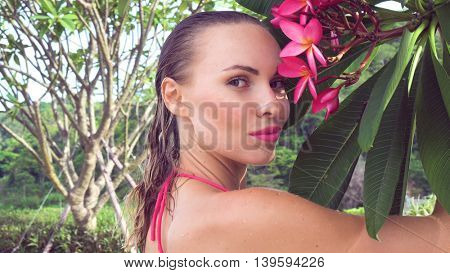 Closeup of sexy young woman wearing bikini with wet hair and tree flower at rooftop on a sunny day
