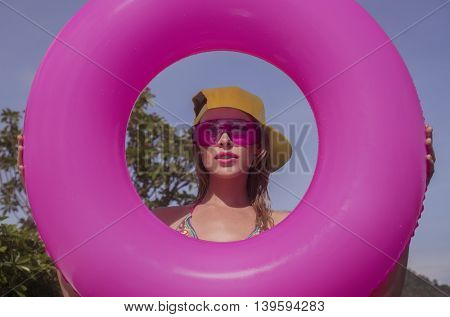 Pretty young woman wearing bikini, yellow hat and purple sunglasses with pink inflatable ring posing in infinity rooftop pool on a sunny day over blue sky and green trees landscape