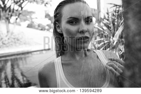 Front view of sexy blonde woman in bikini and white see-through tank top taking outdoors shower on the rooftop surrounded with tropical garden - black and white photo