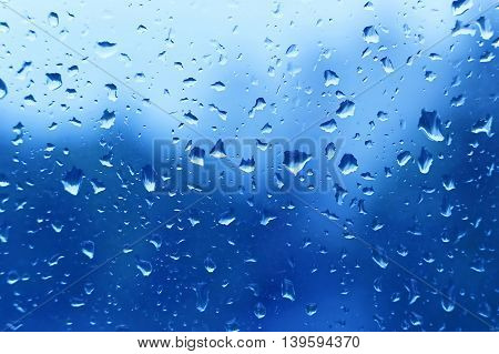 Natural blue background with water drops on glass