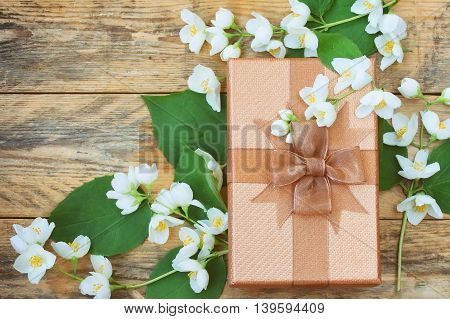 Brown gift box with branches flower jasmine on old wooden table