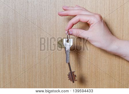 Women's hand holding two keys from the apartment. Wooden background.