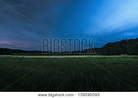 dark evening photo of wheat field with beautiful hop-garden near the village Brozany nad Ohri in czech landscape