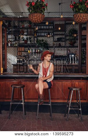 Stylish Young Woman Relaxing At A Cafe With A Drink