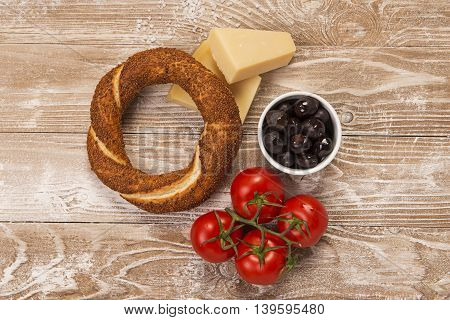 Simit, olives, yellow cheese and tomatoes on whitewashed wood surface