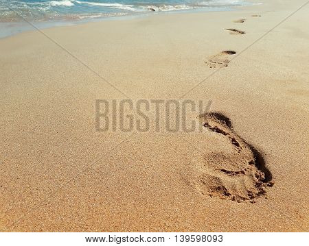 Closeup of footprints in sand at the beach near the water. Journey concept