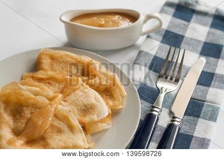 Pancakes Crepes With Caramel Sauce Lay On A Plate