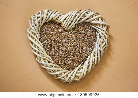 Flax seed in woven heart-shaped basket on light brown background. Copy space