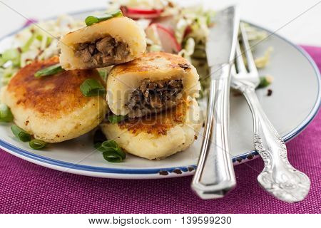 Fried Potato Pies With Mushrooms And Salad On A Plate