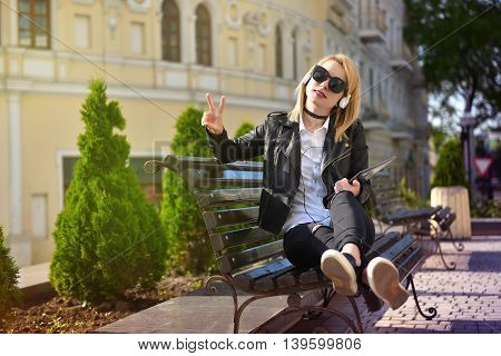 hipster girl with head phones listening to music and showing victory sign
