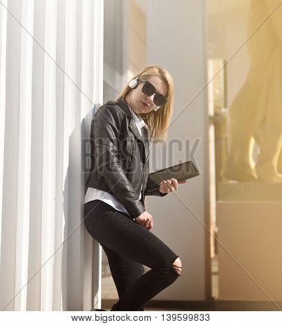 hipster girl with tablet standing near column and listening music