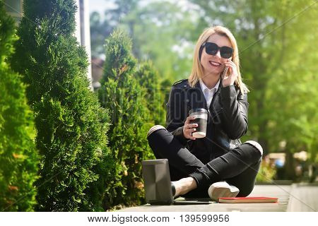 girl sitting with cup of coffee and laptop and talking on the phone