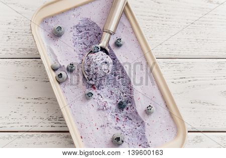 Blueberry ice cream in a container on wooden background