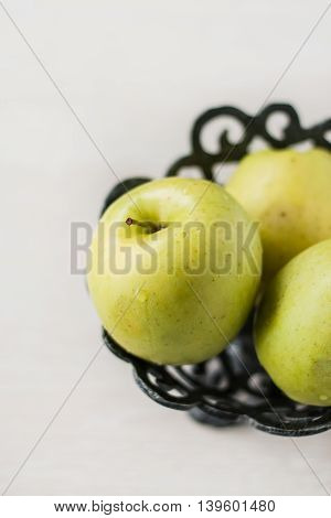 green a apples in a metal a the vase.