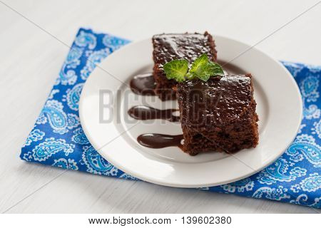 Chocolate Cake On A Plate For Fudge, And Blue Napkin