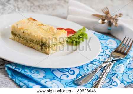 Potato Casserole With Spinach On A Plate And Cutlery