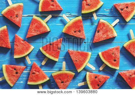 Watermelon slice popsicles on a blue rustic wood background Popular summer fruit with yummy watermelon