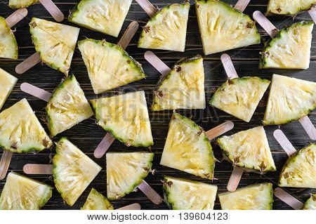 Pineapple slice popsicles on a black rustic wood background Popular summer fruit with yummy pineapple on a stick Flat lay photography of pineapple slice popsicles