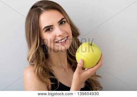 Healthy way of life. Cheerful charming woman smiling and holding an apple while expressing joy on grey background