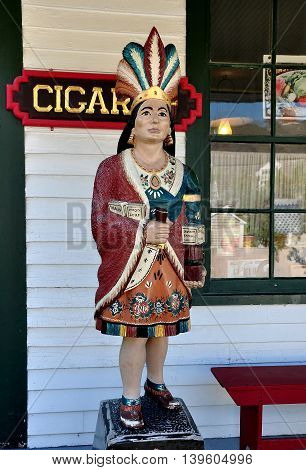 Mystic Connecticut- July 11 2015: A vintage wooden Cigar Store Indian on the porch of the Geo. H. Stone & Co. general store at Mystic Seaport