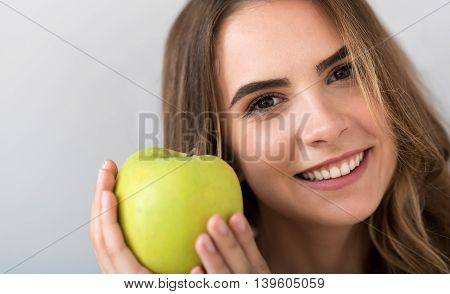 My favorite. Portrait of pleasant cheerful beautiful woman holding an apple and smiling while expressing joy