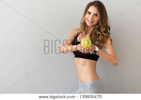 My remedy. Positive charming young woman holding an apple and smiling while feeling content