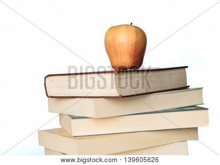 pile of books with an apple on top on the white background