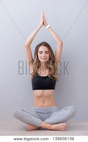 Find inspiration. Pleasant beautiful content woman sitting on the floor and keeping hands together above her head while practicing yoga