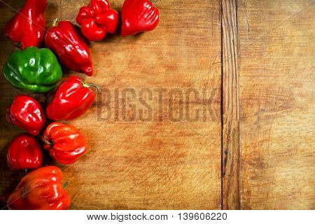 Colorful paprika peppers on a wooden background with copy space on right