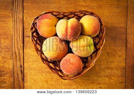 Sweet peaches in a basket on a wooden table