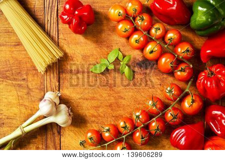 Fresh raw vegetables and pasta on a wood background, directly above