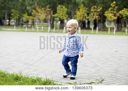 Portrait of blonde baby boy in summer park