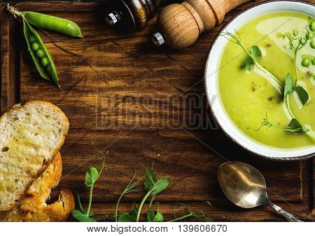 Light summer green pea cream soup in bowl with sprouts, bread toasts and spices over rustic wooden board. Top view, copy space. Food frame concept