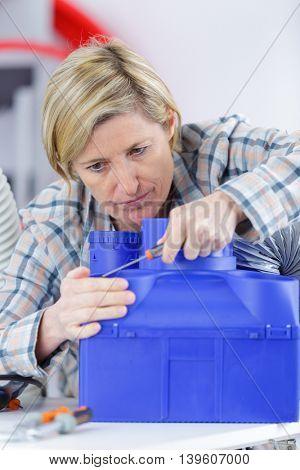 female technician repairing a fan